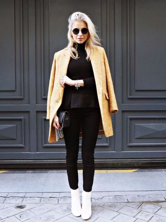 a black sweater, black skinnies, white booties, an amber short coat and a black bag