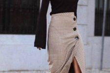 a black top with bell sleeves, a tweed wrap midi skirt with buttons, black sock boots