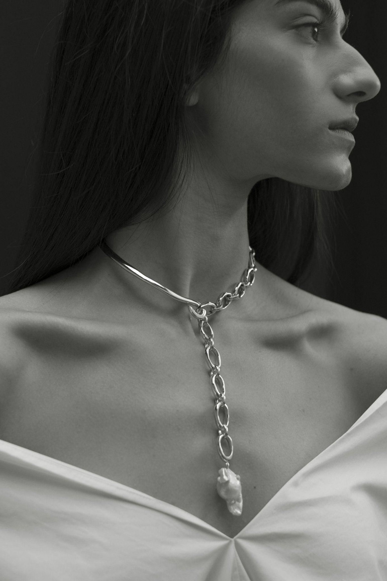 a bold plunging necklace with a sleek and a chain part plus a statement baroque pearl on one end