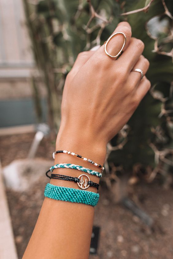 a bracelet stack with colorful touches   turquoise and white plus a chic cactus pendant for a boho feel