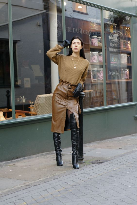 a brown oversized sweater, a brown leather pencil midi with buttons and a slit, black high boots and gloves