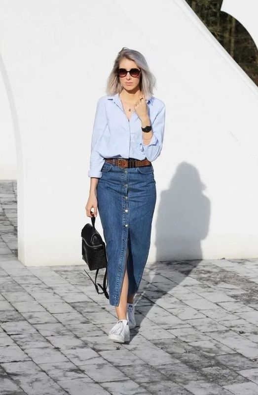 a casual look with an oversized blue shirt, a blue denim pencil midi on buttons and with a slit, white sneakers and a black backpack