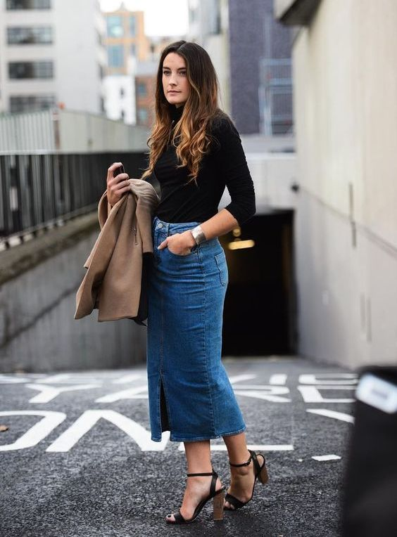 a chic look with a black turtleneck, a blue denim midi skirt with a slit, blakc shoes and a tan coat