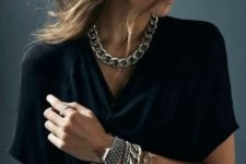 a chunky chain necklace paired with layered bracelets including a matching one for a boho or casual look