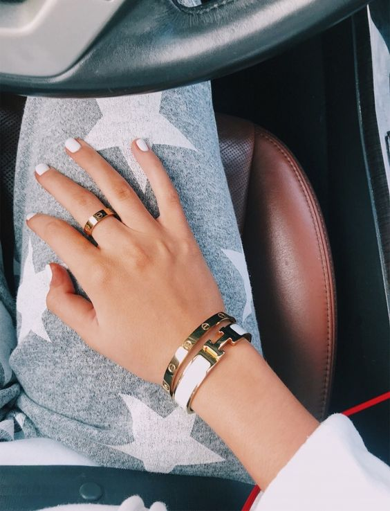 a combo of stylish firm gold bracelets with a white leather touch is super chic and modern