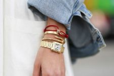a combo of two gold bracelets, a dainty chain bracelet, a watch and a red bracelet with a seashell for an edgy look