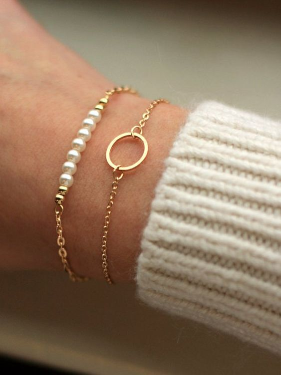 a duo of chic and delicate gold bracelets with pearls and a circle pendant for a girlish look