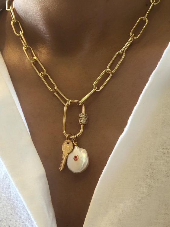 a gold chunky chain necklace with a baroque pearl and a key pendant features two trends - heavy chains and pearls