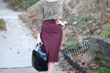 a leopard print top with long sleeves, a high neckline, a burgundy leather midi with a front slit, a black bag and shoes