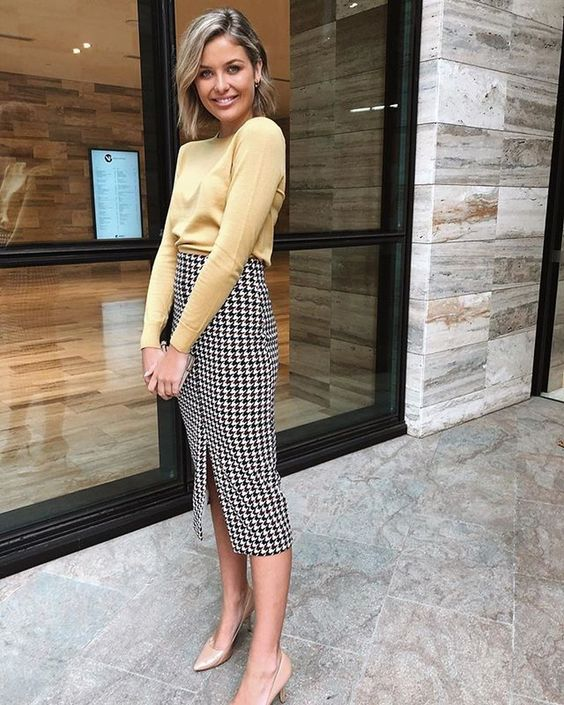 a marigold top with long sleeves and a high neckline, a printed pencil midi skirt with a front slit and tan heels