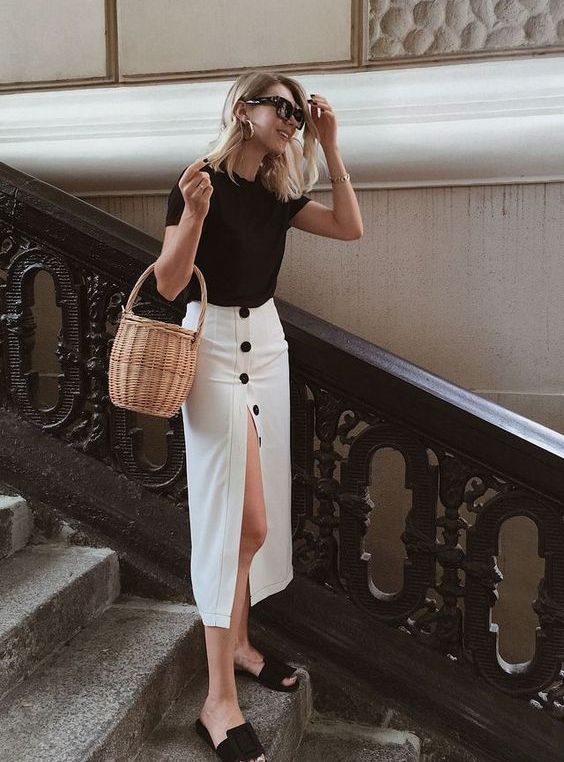 a monochromatic look with a black tee, a white pencil skirt with blakc buttons and a slit, black buckle shoes and a basket