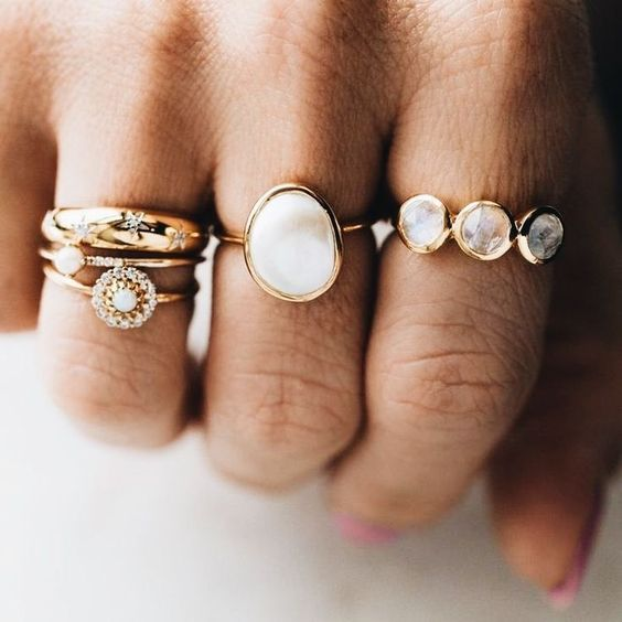 a number of stacked gold rings with moonstones and diamonds that vary in shapes but still match