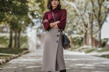 a purple oversized sweater, a plaid midi wrap skirt on buttons, black tall boots and a black bag