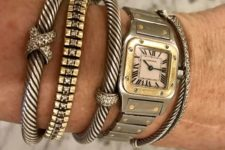 a stack of bold metallic bracelets with pretty embellished charms and a watch – all the pieces are statement ones