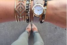 a stack of bracelets with beads, a statement geometric one and a watch on a grey leather strap