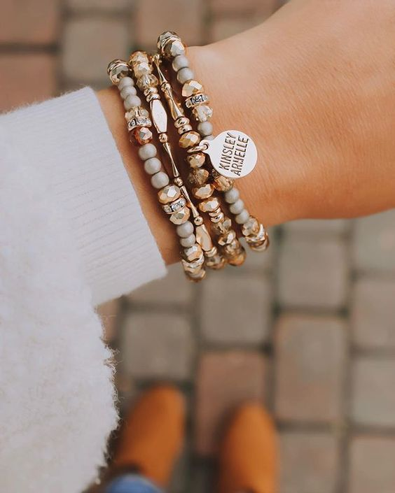 a stack of chic and elegant bracelets with gold and stone beads plus a personalized metal tag for an ultimate look