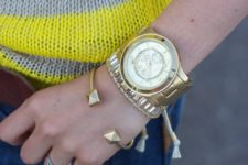 a stack of gold and silver bracelets -cuffs, embellishments and a matching watch as the main piece