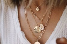 a stack of statement necklaces, with chunky chains and bold pendants including a seashell