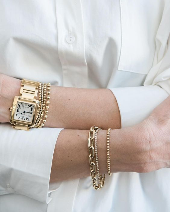 a stack of three different bracelets in various finishes and looks, a heavy chain is a cool trend