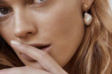 a statement baroque pearl earring with a tiny gold shell is a stylish and refined idea for a trendy look