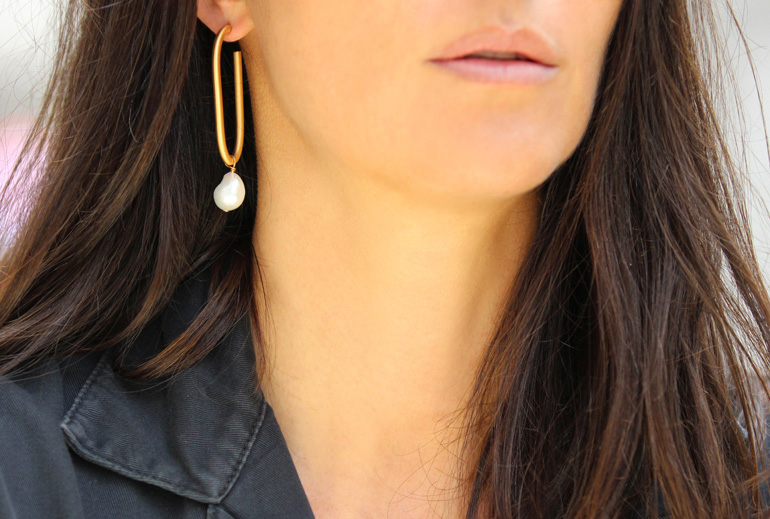 a statement gold bracket and baroque pearl earring features two trends - pearls and a mono earring