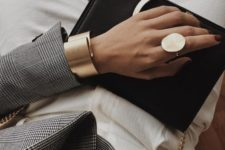 a statement matte gold ring of an irregular shape and a matching bracelet that is also a statement