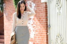 a tan top with buttons, a grey plaid midi with a front slit, a brown bag and a tan blazer