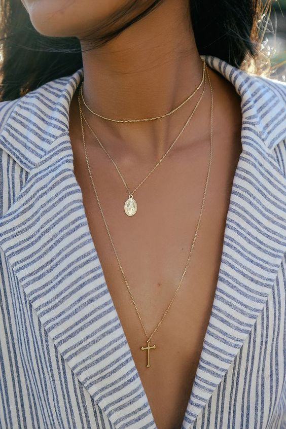a trio of delicate gold necklaces including a choker, a plunging one with a cross and a little icon