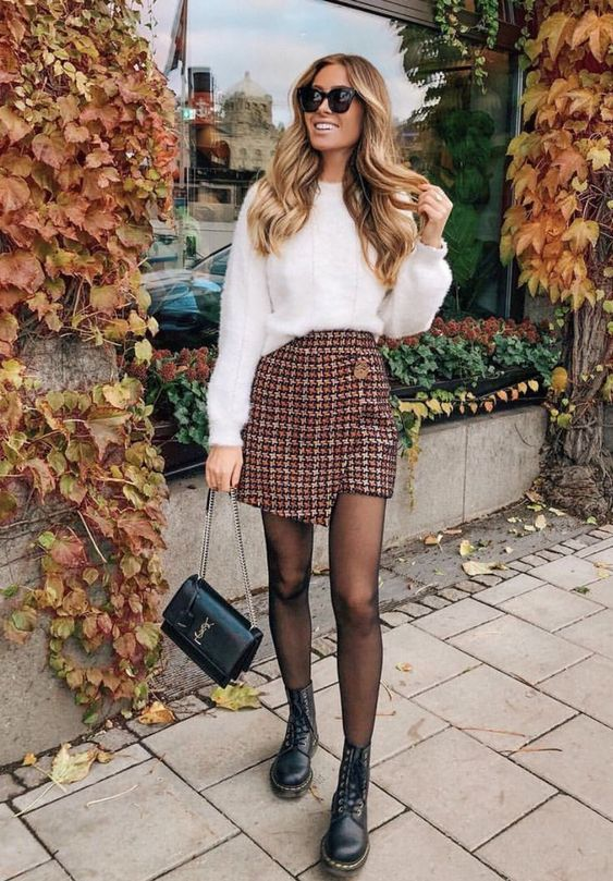 a white fluffy sweater, tweed wrap mini skirt, black boots and a black bag for a warm day