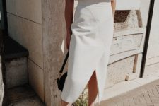 a white oversized tree, a white pencil midi with asymmetry and a front slit, white mules for a minimal summer look