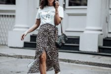 a white printed tee, a leopard print midi skirt with a front slit, white sneakers and a black bag on chain