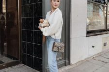 a white sweater, blue cuffed jeans, white booties with heels and a printed crossbody bag