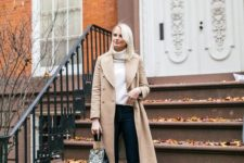 a white turtleneck sweater, black skinnies, white heeled booties, a tan coat and a printed bag