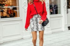 an oversized red sweater, a snake print mini, white heeled booties and a black crossbody bag