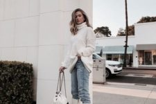 an oversized white sweater, light blue jeans, white knee boots and a black and white backpack