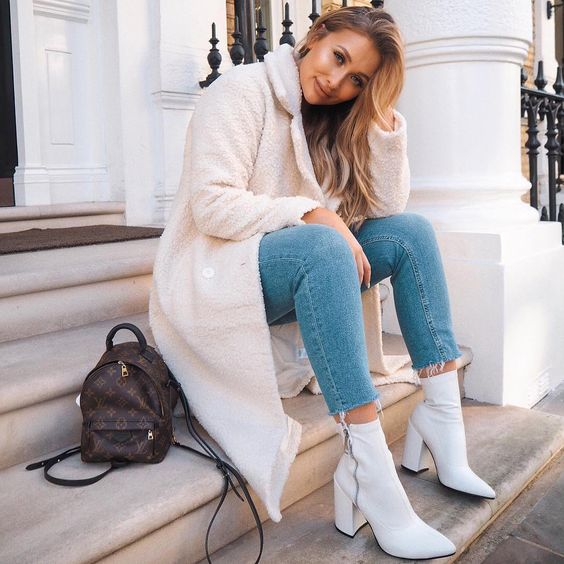 blue skinnies with a raw hem, white heeled booties, a white faux fur midi coat and a brown backpack