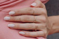 multiple rose gold rings including texturala nd rhinestone ones look very tender and boho-like