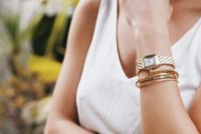 several gold bracelets with a pretty shape and a statement watch that matches in finish for a cool look
