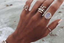 stacked gold constellation-inspired rings of gold and silver, with rhinestones and a large statement stone