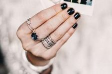 stacked silver rings with various shapes that complement and a single one with a black rhinestone