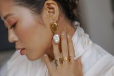 statement gold and baroque pearl earrings plus matching gold and pearl rings for an ultimate modern look