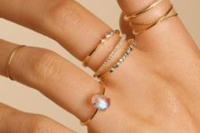 thin stacked gold rings with diamonds and a moonstone are different in textures and shapes and create a catchy look