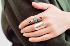 two statement rings – a polished silver statement one and a red and green rhinestone ring