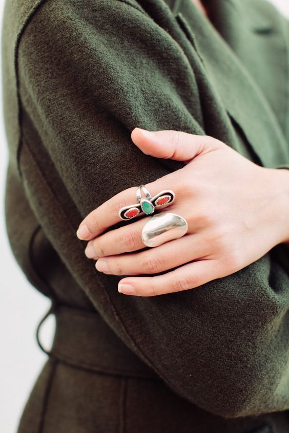 two statement rings - a polished silver statement one and a red and green rhinestone ring