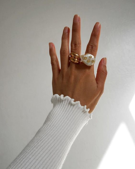 two statement rings - a rose gold swirl one and a baroque pearl one with gold dots for a girlish look