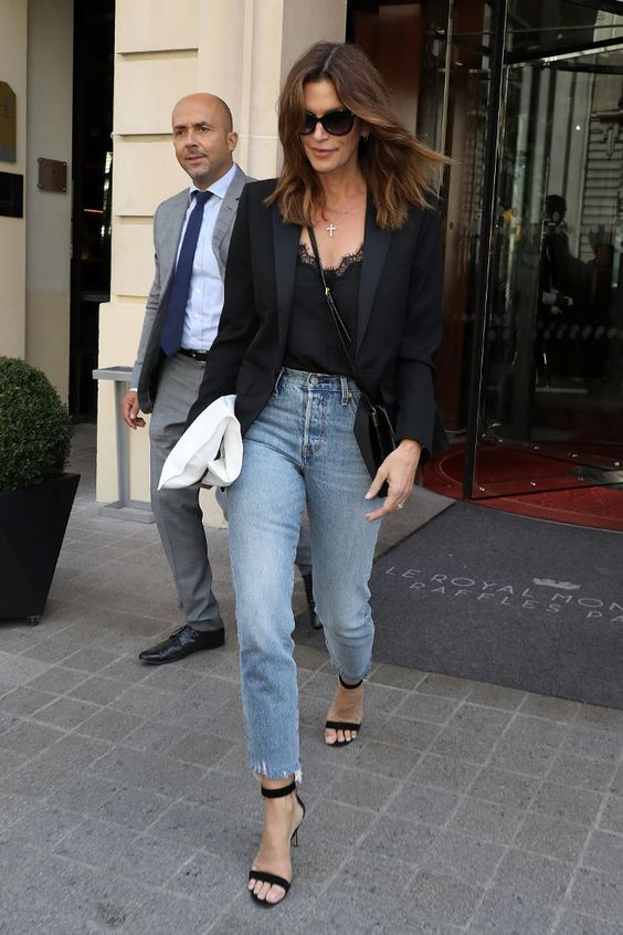a black lace top, a black blazer, black shoes and light blue straight jeans with a raw hem