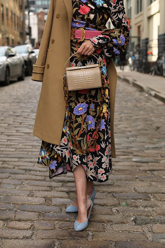 a bright yet moody floral midi dress with a pink belt, blue shoes, a camel bag and a camel coat