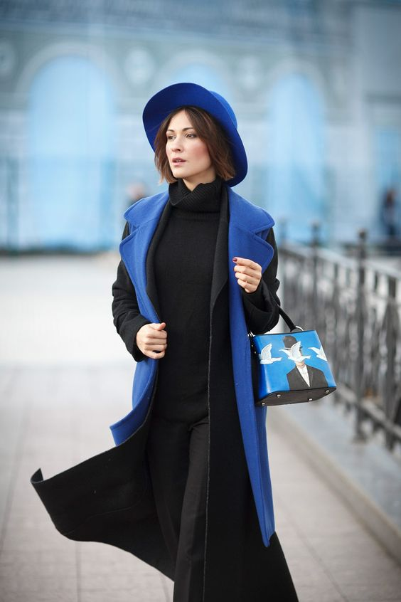 a monochromatic winter outfit of a black turtleneck, pants, a coat, a blue waistcoat, hat and a bag