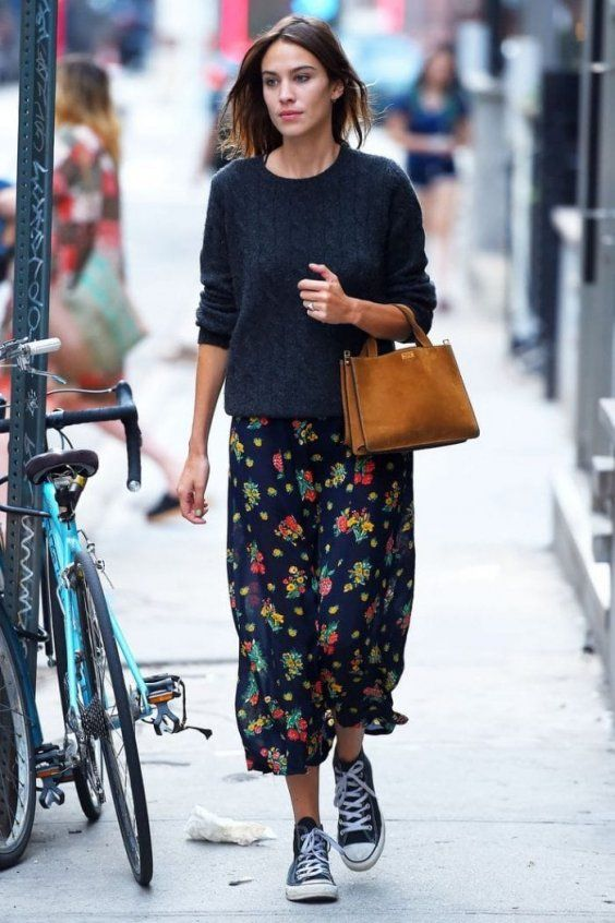 a black sweater, a dark floral print skirt, black sneakers and an amber bag for a hipster look