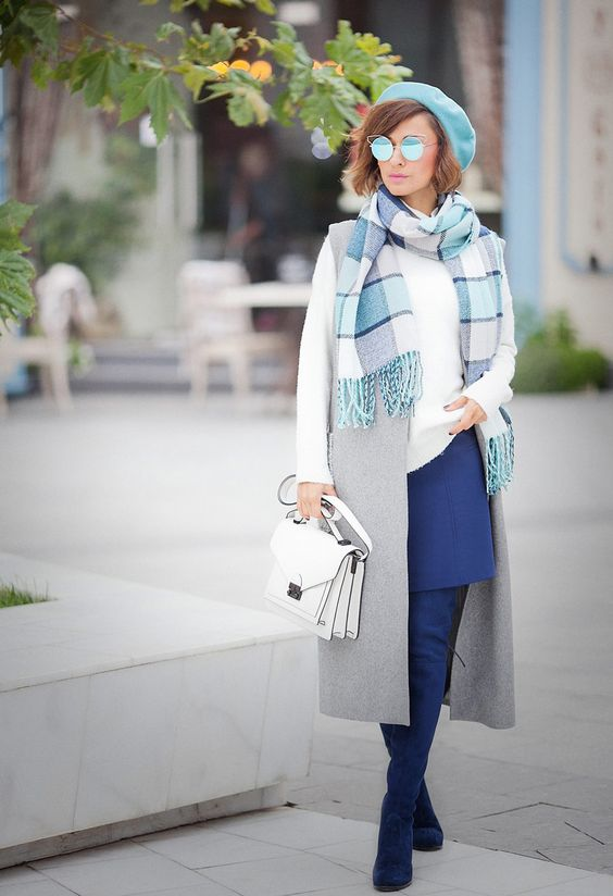 a chic look with a white sweater, a grey waistcoat, a blue skirt and boots, a beret, a scarf and a bag